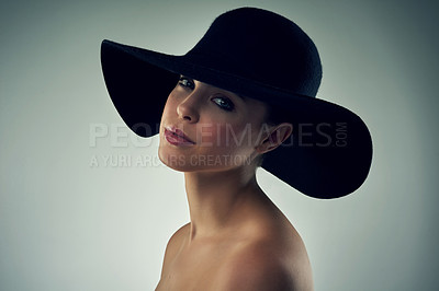 Buy stock photo Studio portrait of a beautiful young woman wearing a hat against a grey background