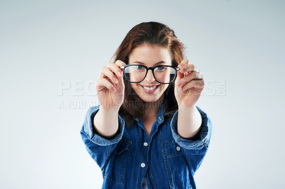 Buy stock photo Studio portrait of a young woman holding a pair of spectacles against a grey background