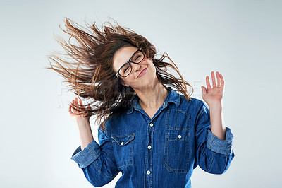 Buy stock photo Studio shot of a young woman flipping her hair against a grey background
