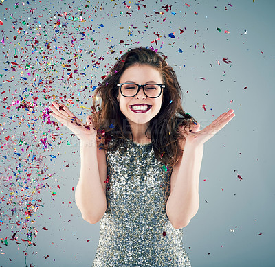 Buy stock photo Studio shot of a young woman with confetti falling around her against a grey background