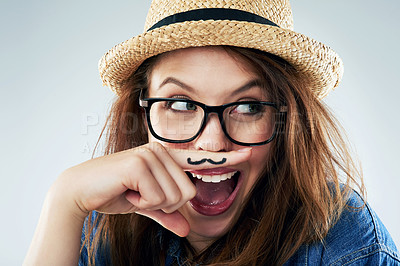 Buy stock photo Studio shot of a young woman holding her finger under her nose with a moustache drawn on it