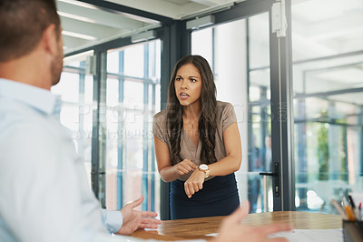 Buy stock photo Shot of an angry businesswoman scolding her colleague for being late in the office