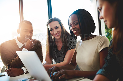Buy stock photo Shot of a group of young businesspeople working together around a laptop in the office