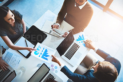 Buy stock photo High angle shot of a team of businesspeople working around a table in the office