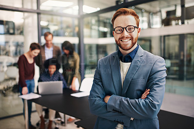 Buy stock photo Portrait of a confident young man standing in a modern office with his colleagues in the background