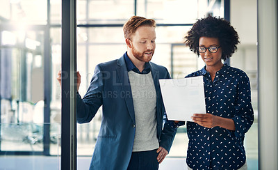 Buy stock photo Shot of two colleagues reading a document together at work