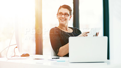 Buy stock photo Shot of a thoughtful young businesswoman working at her desk in an office