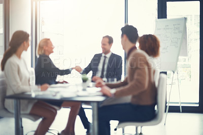 Buy stock photo Shot of a two corporate colleagues shaking hands during a boardroom meeting