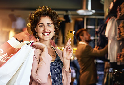 Buy stock photo Shot of a woman holding up her credit card while out shopping