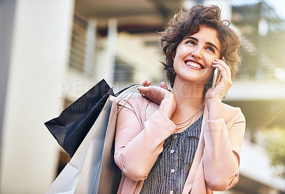 Buy stock photo Cropped shot of a young woman talking on her phone while out shopping