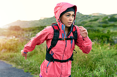 Buy stock photo Shot of a focused young woman out for a run on a cool morning