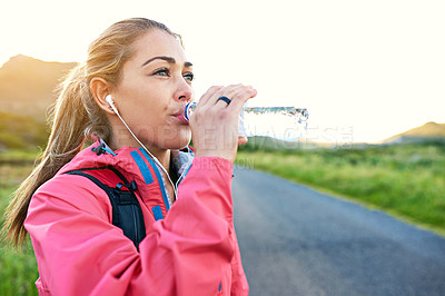 Buy stock photo Shot of a young woman drinking from a water bottle while taking a break from an early morning run