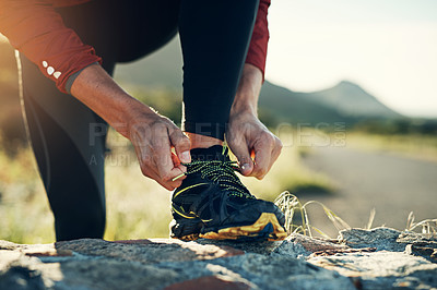 Buy stock photo Cropped shot of a young man tying up his running shoes while out for a jog