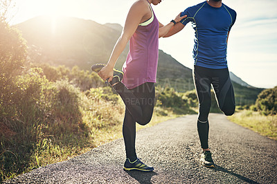 Buy stock photo Cropped shot of two friends stretching before an early morning run