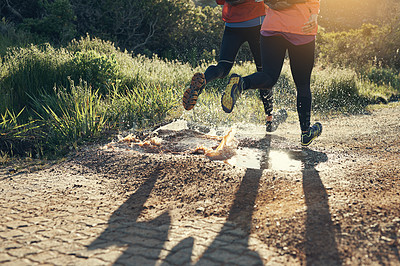 Buy stock photo Cropped shot of two friends' legs while out for a run together on a cool morning