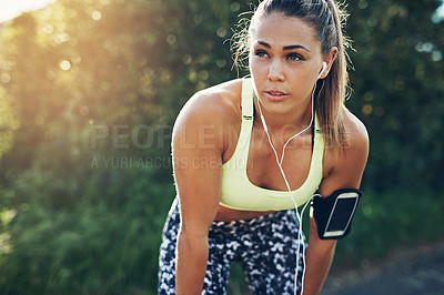 Buy stock photo Shot of a focused young woman listening to music on headphones before going for a run