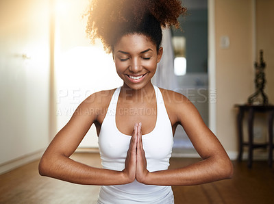 Buy stock photo Cropped shot of a sporty young woman practicing yoga indoors