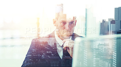 Buy stock photo Shot of a focussed businessman using his computer superimposed over a cityscape