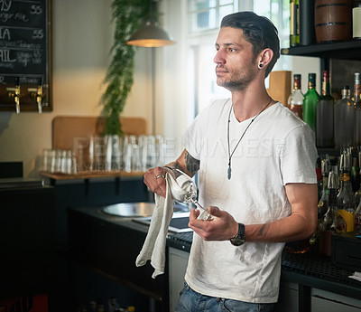 Buy stock photo Shot of a young waiter daydreaming while polishing a glass behind the bar