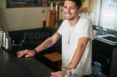 Buy stock photo Shot of a happy young bartender standing behind the counter in a bar