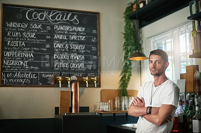 Buy stock photo Portrait of a serious young bartender posing with his arms crossed behind the bar