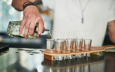 Buy stock photo Cropped shot of an unidentifiable bartender pouring shots behind the bar