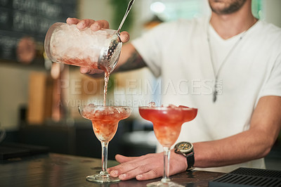 Buy stock photo Cropped shot of an unidentifiable bartender pouring a cocktail behind the bar