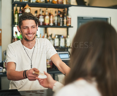 Buy stock photo Shot of a friendly young bartender accepting a card payment from a customer