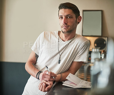 Buy stock photo Portrait of a serious young bartender leaning on the bar counter