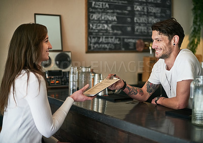 Buy stock photo Shot of a friendly young bartender helping a customer with her order across the bar counter