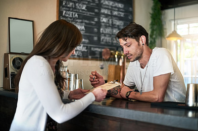 Buy stock photo Shot of a young bartender helping a customer with her order across the bar counter