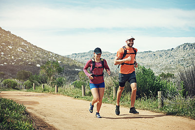 Buy stock photo Shot of two young friends running together along a path outdoors