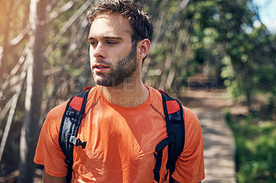 Buy stock photo Shot of a focused young man out for a run on a trail in a forest