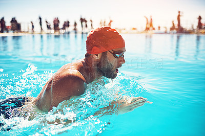 Buy stock photo Shot of an athletic young man swimming in a pool
