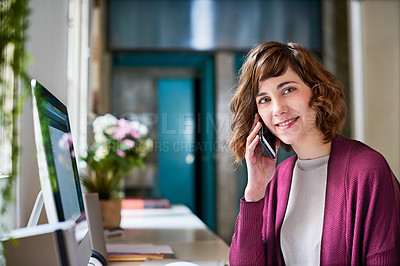 Buy stock photo Portrait of a young woman talking on a cellphone at her computer in her home office