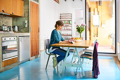 Buy stock photo Portrait of a young woman sitting at her kitchen table using a digital tablet