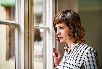 Buy stock photo Shot of a young woman looking out through a window at home