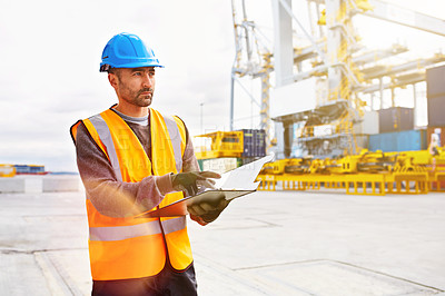 Buy stock photo Shot of a young man in workwear with a clipboard  standing outside on a large commercial dock