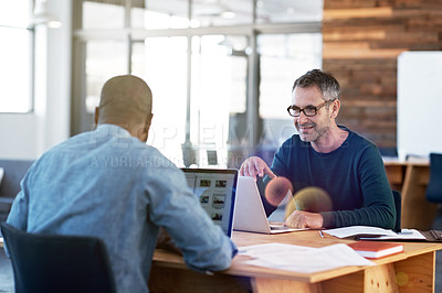Buy stock photo Shot of two men working together at a table in an office