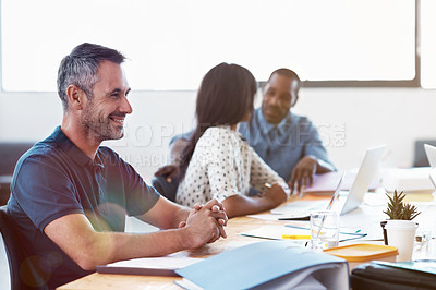 Buy stock photo Shot of a smiling office worker with colleagues sitting in the background