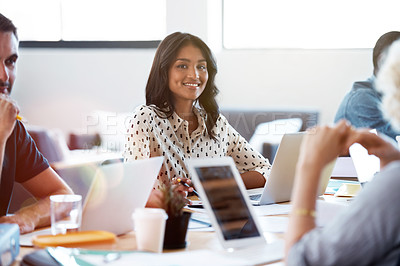 Buy stock photo Portrait of a smiling woman sitting in an office working on a laptop surrounded by colleagues