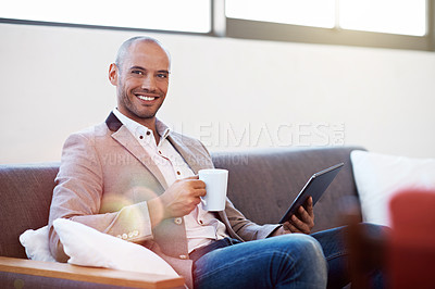 Buy stock photo Portrait of a young man sitting on a sofa in an office drinking coffee and using a digital tablet