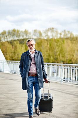 Buy stock photo Portrait of a mature man pulling a suitcase while walking over a bridge in the city
