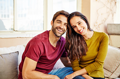 Buy stock photo Portrait of a young couple relaxing together on their living room sofa