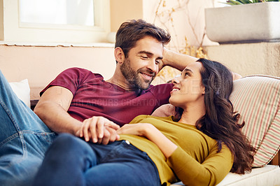Buy stock photo Shot of a smiling young couple talking together while relaxing in their living room