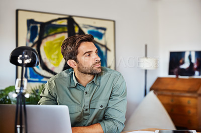 Buy stock photo Shot of a young man sitting at a table at home working on a laptop