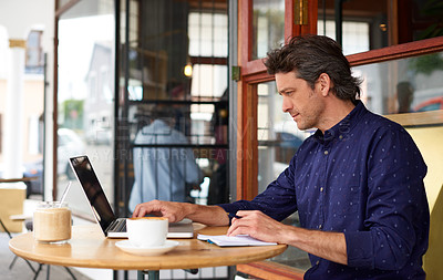 Buy stock photo Shot of a man working on a laptop at a sidewalk table outside of a cafe
