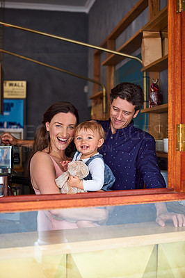 Buy stock photo Portrait of smiling couple and their little girl looking through the window of their cafe
