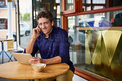 Buy stock photo Shot of a mature man sitting on patio table at a cafe using a tablet and cellphone