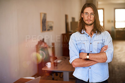 Buy stock photo Portrait of a focused young designer standing with his arms crossed in an office